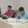 Dois jovens sentados , um trabalhando no computador e outro escrevendo em caderno e manuseando processos