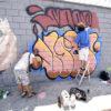 Homens pintando o muro com spray