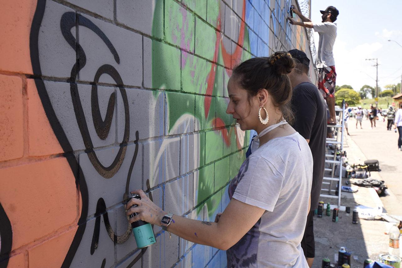 Mulher desenhando em muro