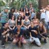 Foto posada em grupo de jovens em calçada em frente a um bosque de árvores