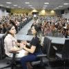 Janinne, com ajuda da intérprete, assiste a palestra do simpósio