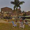 Prédio de tijolos à vista no fundo, com barracas e cadeiras de praia sobre gramado, com lâmpadas acesas em horário de entardecer