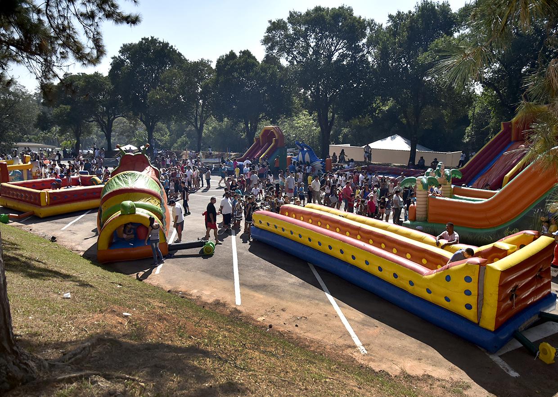 Brinquedos infláveis em estacionamento, com crianças e adultos em fila