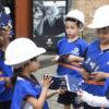 Crianças com coletes e capacetes personalizados , segurando passaportes e conversando