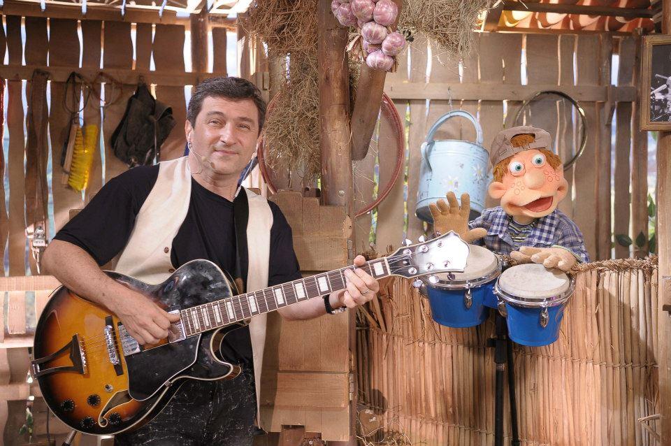 Homem cantando, segurando violão, em cenário de fazenda, com boneco em formato de criança tocando tamborins