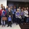 Representantes das famílias contempladas posam para foto no gabinete do prefeito Luiz Fernando Machado