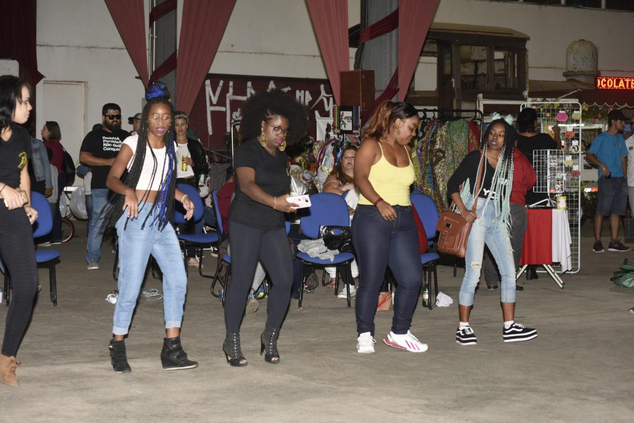 Adolescentes dançando uma ao lado da outra, com pessoas sentadas ao fundo