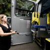 Mulher opera controle para descida de cadeira adaptável para deifientes em ônibus