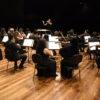 Palco de teatro, com fundo escuro, e músicos sentados, atentos à regente em pé