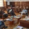 Pessoas conversando, sentadas ao redor de mesa, em sala com decoração de madeira