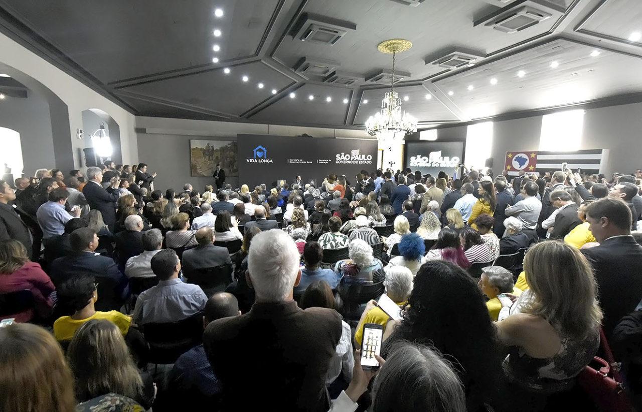 Salão de cerimônia com pessoas sentadas e em pé, assistindo à apresentação