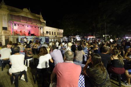 Foto noturna da praça com coreto ao fundo e plateia sentada assistindo à apresentação