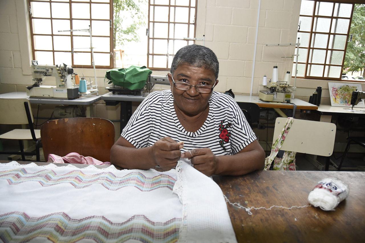 Mulher olhando para a foto enquanto faz crochê e bordado em tecido apoiado em mesa, com janelas e máquinas de costura ao fundo