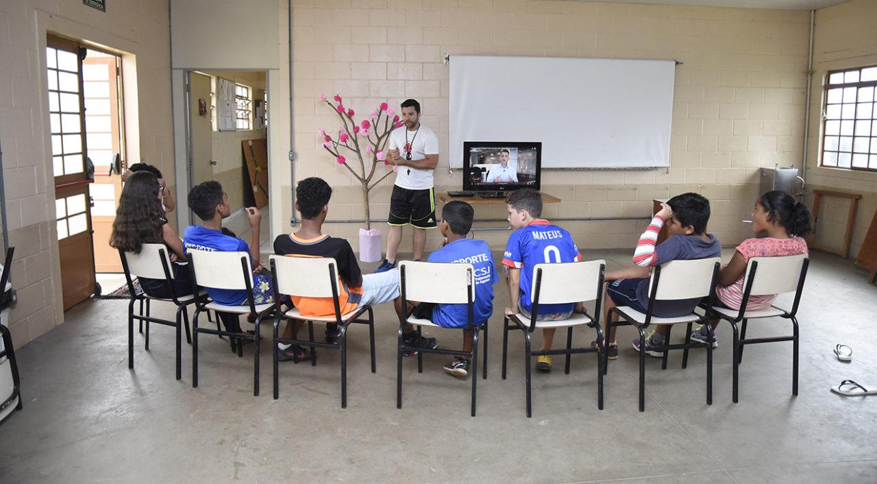 Crianças sentadas em cadeiras, assistindo a uma televisão, com professor falando à frente da sala