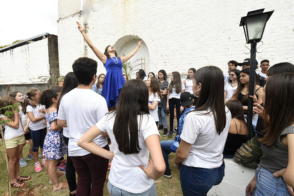 Atriz em encenação em lugar elevado em relação a grupo de jovens estudantes que assistem