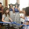 Duas meninas usam tesoura para cortar faixa de inauguração