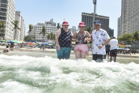 Três pessoas entrando na água do mar, com prédios ao fundo