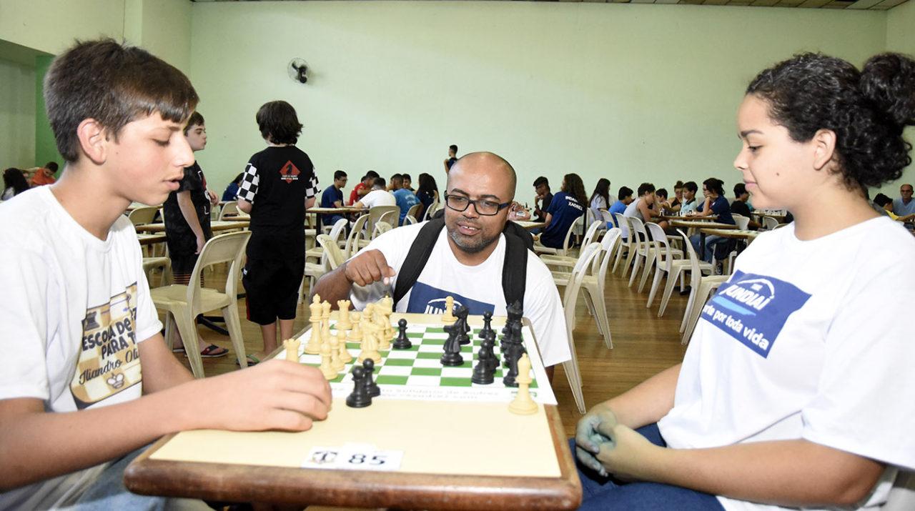 Menina e menino jogando xadrez