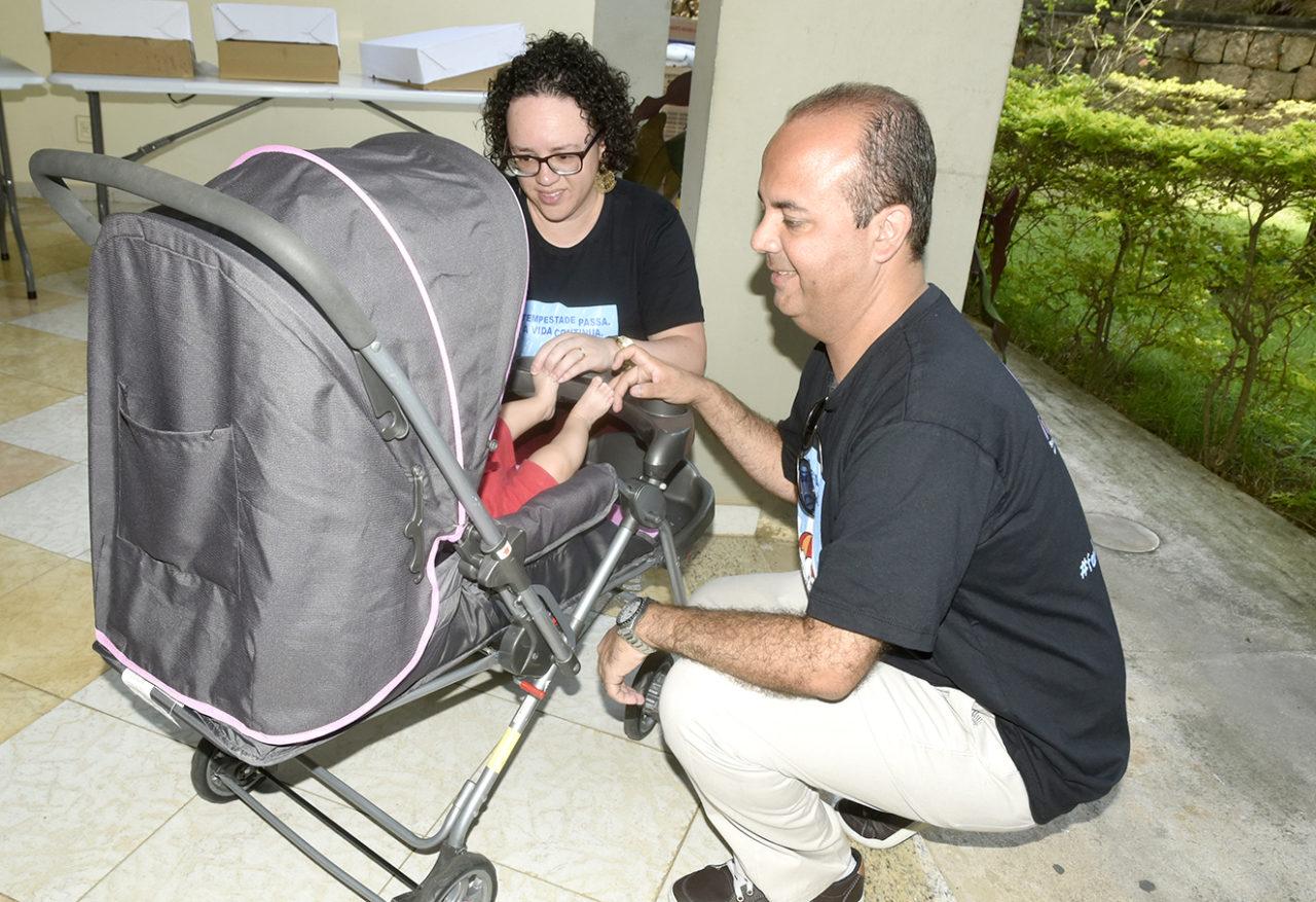 Homem e mulher abaixados, brincando com bebê dentro de carrinho