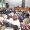 Auditório com pessoas sentadas e autoridades sentadas em palanque