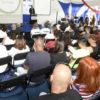 Auditório com cadeiras ocupadas e homem à frente falando em púlpito
