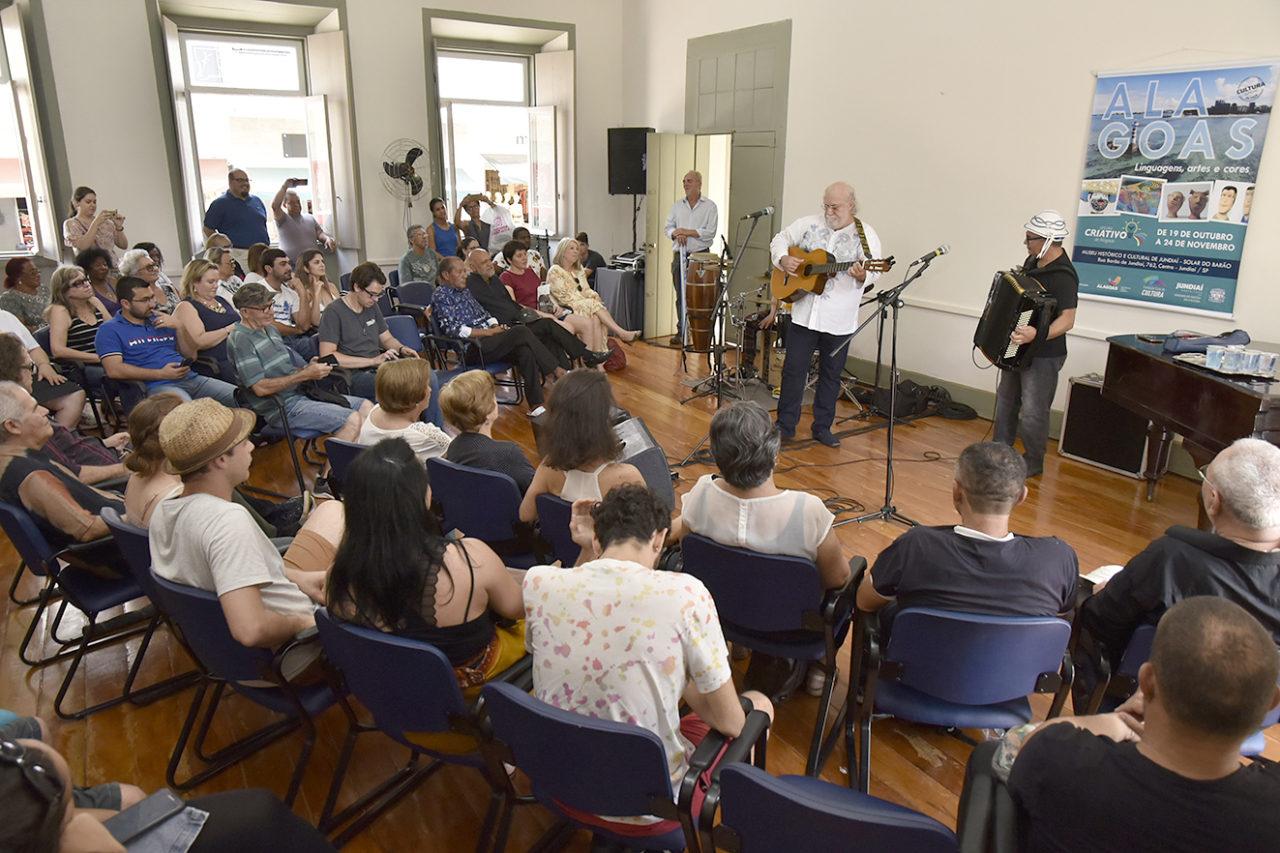 Show musical, com pessoas sentadas e músicos em pé