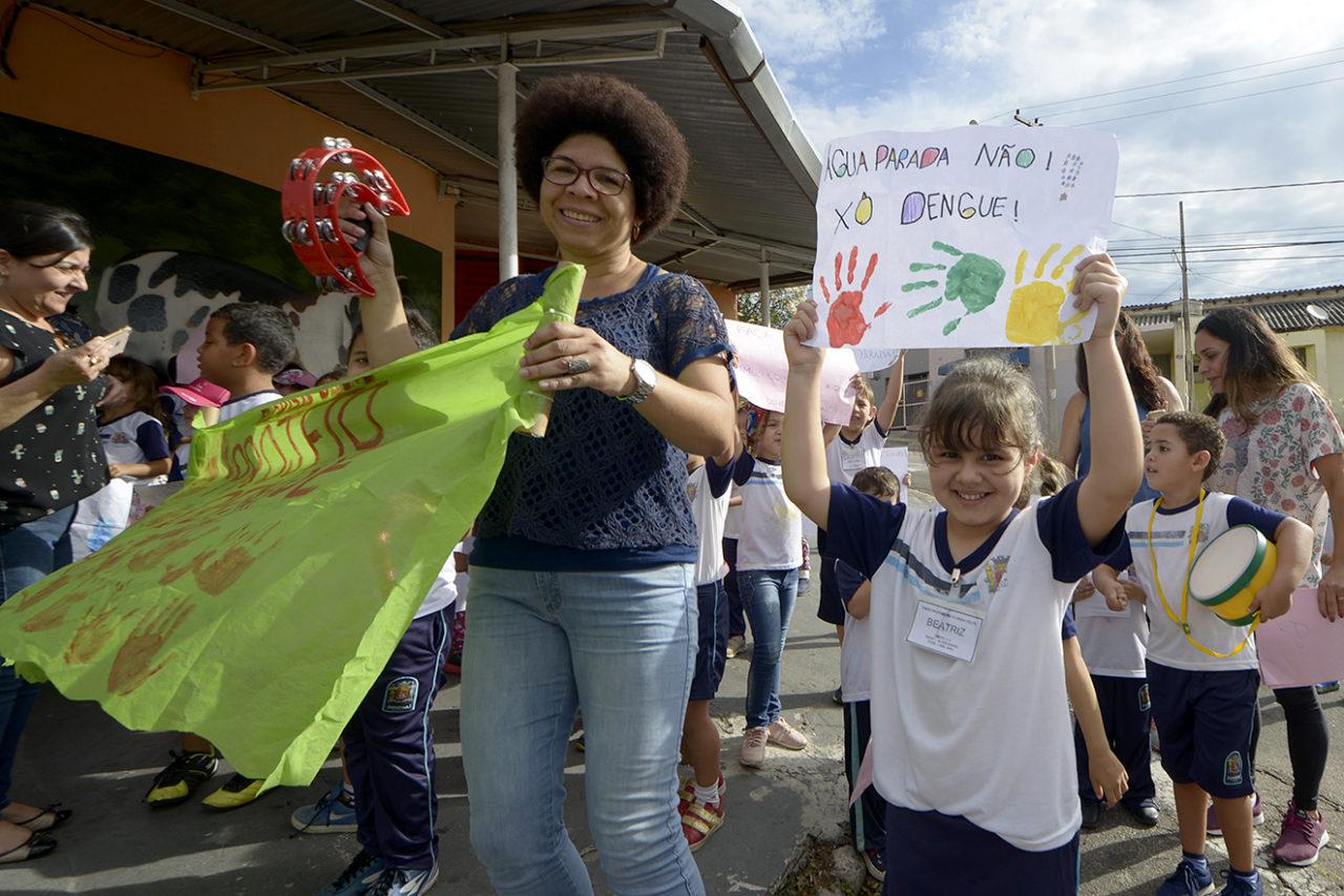 """Beatriz mostra, orgulhosa, seu cartaz: """"Água parada não!"""""""