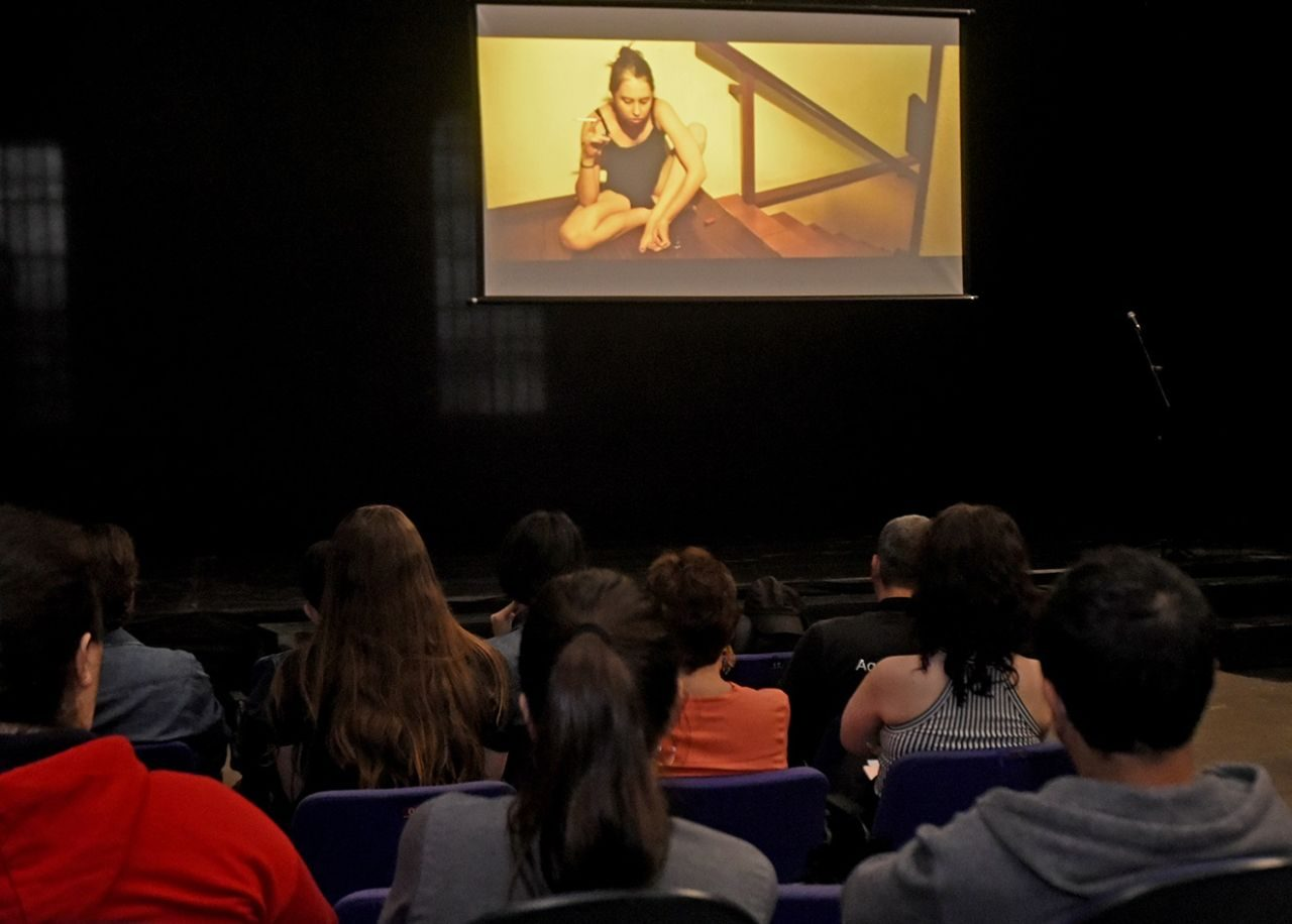 Sala de cinema, com público e filme sendo exibido no telão