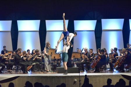 Orquestra se apresentando em palco, com bailarinos se apresentando à frente
