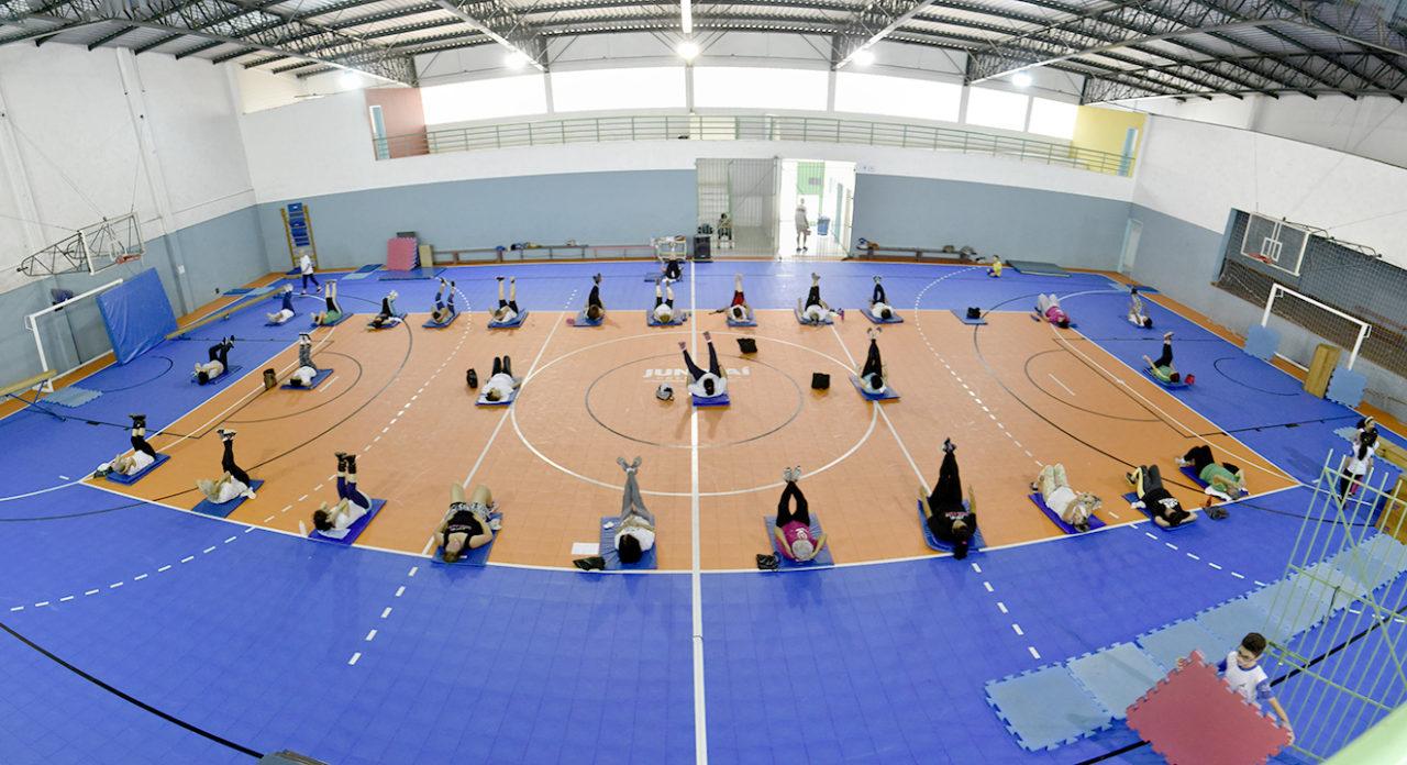 Foto do alto de quadra coberta, com pessoas fazendo ginástica em colchões