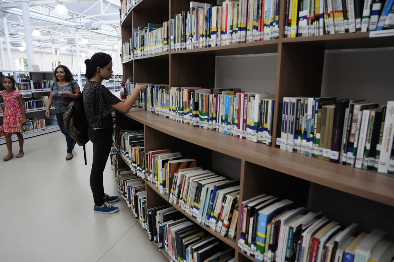 Mulher olha livros em estante, com mulher e menina passando ao fundo