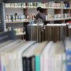 Prateleiras com livros e pessoa ao fundo buscando algum item