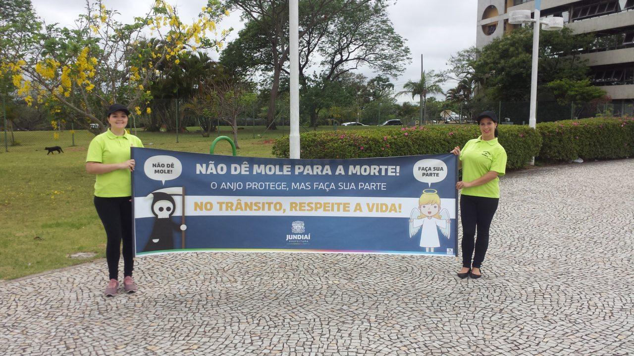 Agentes de trânsito de Jundiaí seguram faixa com o slogan da campanha em frente ao Paço Municipal