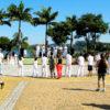 Grupo jogando capoeira em praça com palmeiras e represa ao fundo