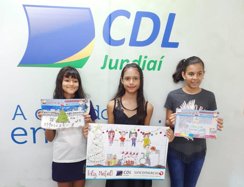 Alunas de Emeb mostram cartazes que desenharam para concurso
