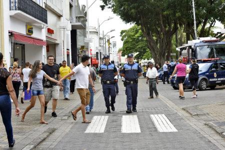 Guardas municipais cuniformizados caminhando em calçadão de pedestres no Centro
