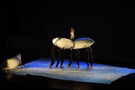 Bailarinos em performance no palco, com travesseiros e lençóis gigantes