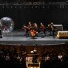 Palco de teatro, com apresentação de bailarinos, e de orquestra abaixo