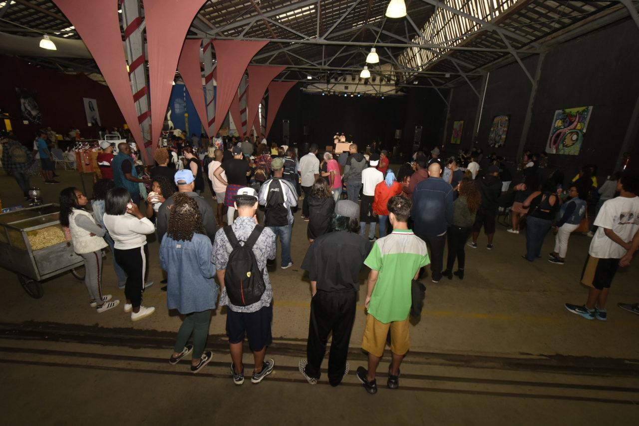 Galpão coberto, com pessoas assistindo a uma apresentação em palco