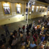Foto do alto de calçadão com pessoas assistindo a apresentção de pessoas cantando em janelas de prédio histórico