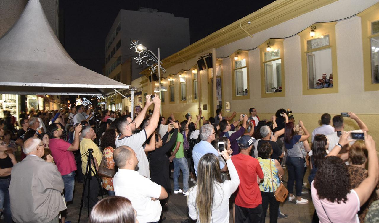 Pessoas em calçadão de pedestre assistindo a uma apresentação de música nas janelas de prédio histórico