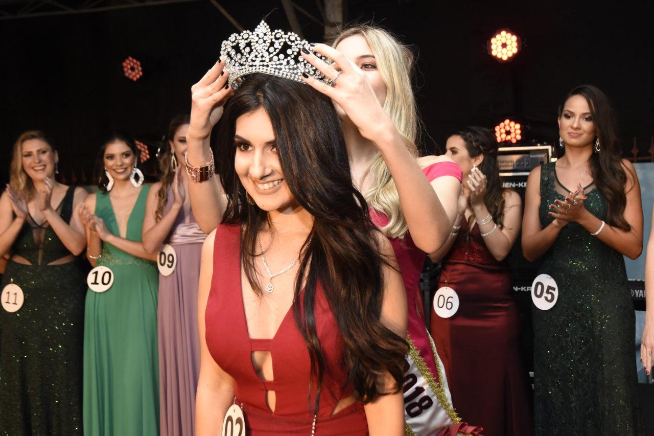 Mulher coloca a coroa na cabeça de outra, com outras mulheres em pose para foto