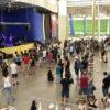 Pavilhão coberto, com pessoas em pé assistindo a show em palco
