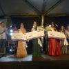 Mulheres em traje de gala com cheque simbólico