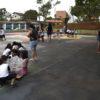 Crianças brincando em quadra escolar, com cachorros na coleira e gaiolas