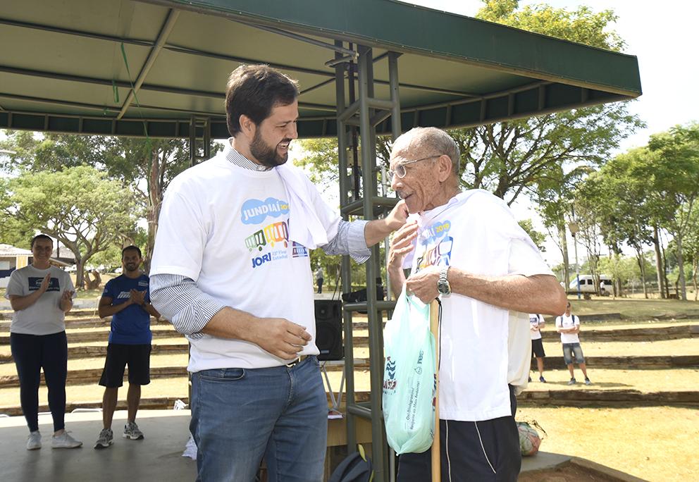 Homem conversando com idoso, entregando camiseta