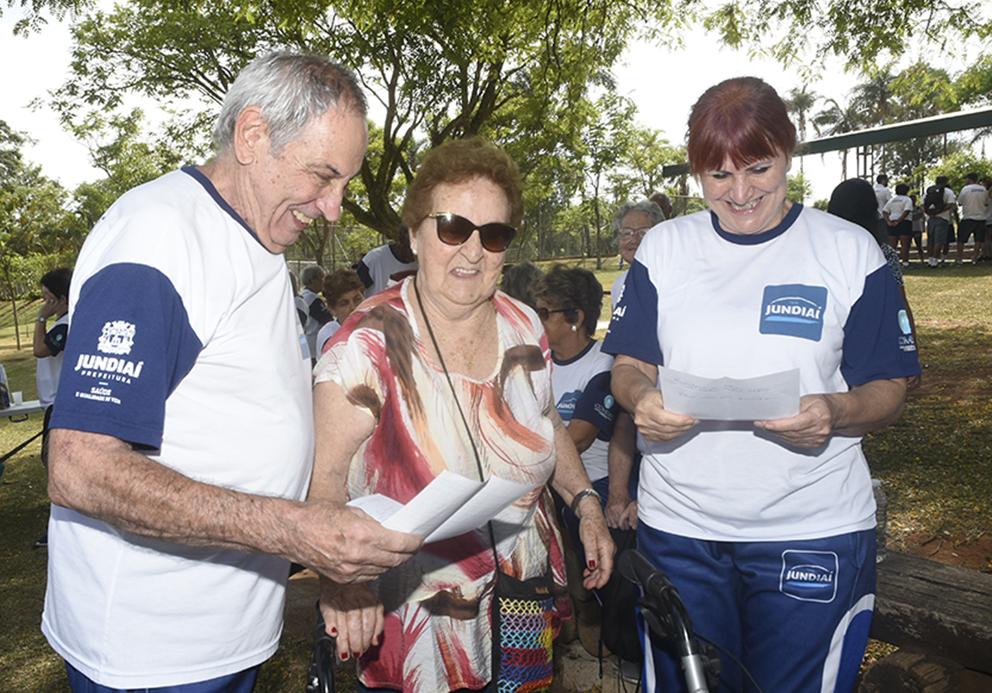 Um homem e uma mulher idosos segurando uma folha de papel, ladeando outra mulher idosa apoiada em andador