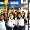 Crianças com uniforme escolar cantando em frente a painel