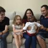 Crianças e adultos sentados em sofá, olhando para bebê de colo, com um bebê de colo, de costas