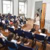 Crianças sentadas em cadeiras, assistindo a uma apresentação de uma contadora de histórias
